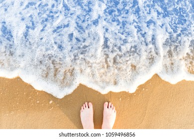 Woman's feet on yellow beach sand with sea wave and white foam