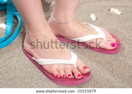 85324e195b46 A woman s feet in pink flip flops on the sand with a pedicure and pink nail