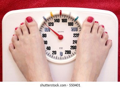 Woman's feet with red toenail polish on a white bathroom scale