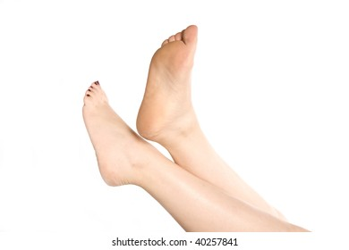 A woman's feet relaxed and pointing upwards with her toes painted red.