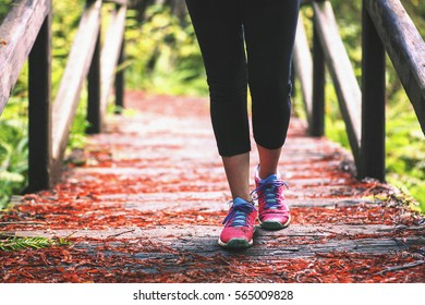 A woman's feet as she walks across a bridge in a green forest