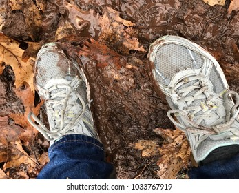 Woman's feet with sneakers on muddy ground with leaves