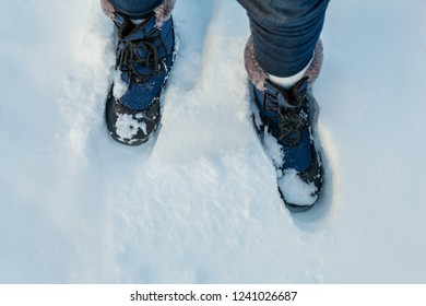 Woman's feet in snow boots in deep snow. Iceland