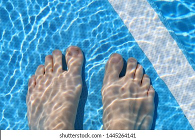 Woman's feet underwater in clear, shallow pool water. High angle view. This photo shows the toes and feet of a female and the bottom of a pool during a sunny vacation day. You can also see small waves