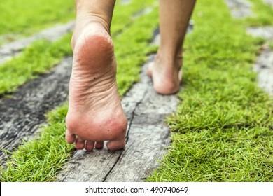 Frauenfüße, die auf dem Gras spazieren. Altholz