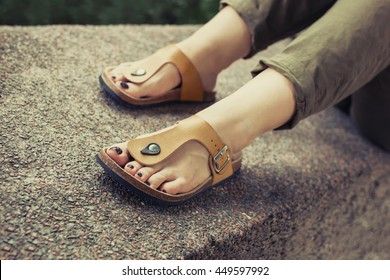 Woman's feet in yellow stylish summer sandals with dark nail polish, in green summer pants sitting on the wall