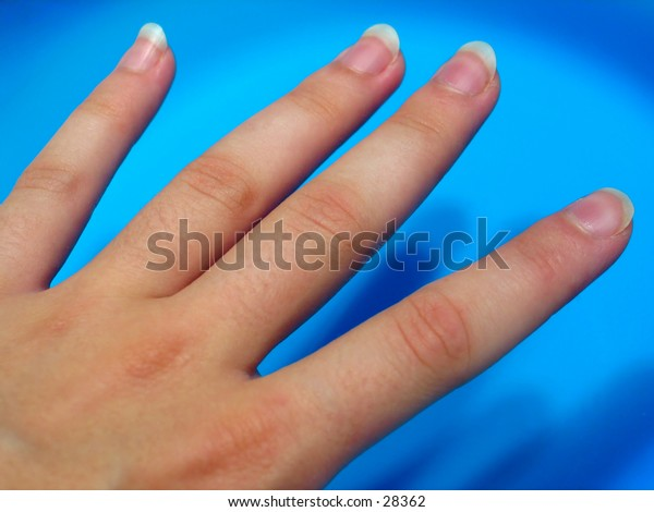 Woman's fingers against a bright blue surface