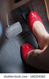 A woman's foot depressing the brake pedal of a car.