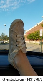 Womans foot in a shoe on the dashboard