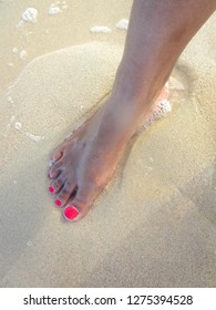 Woman's foot with toenail polish in the water with sand