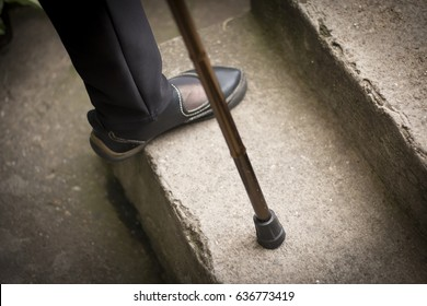 Woman's foot and walking stick stepping up stairs
