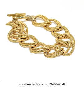 A woman's gold chain bracelet on white.