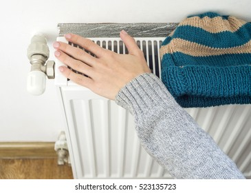 Woman's Hand Adjusting Heater Thermostat in winter time