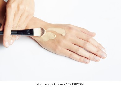 A woman's hand applying make up on the skin with brush.