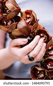 Woman's hand with a beautifully done nails holding a brown cymbidium flower, close up vertical view