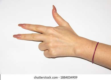 Woman's hand with bent two fingers and a red thread on the wrist. Female hand have a long nails and show three fingers