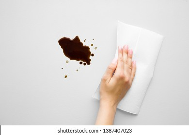 Woman's hand cleaning fresh spilled dark beverage from gray desk. Coffee stain simple removing with white paper napkin. Cleanup. Close up.