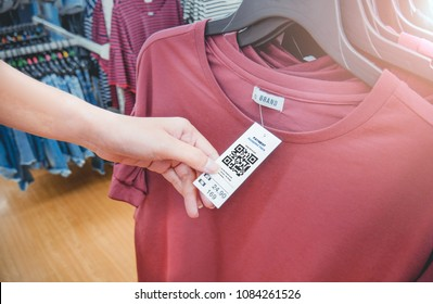 Woman's hand with a cloth hang tag label with QR code in a clothing shop lighting effect.