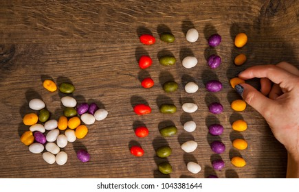woman's hand collects even row of colorful candies on a wooden background. top view with copy space