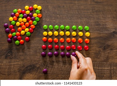 woman's hand collects even row of colorful candies on a wooden background