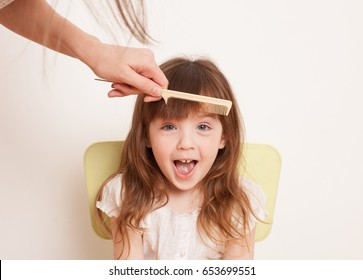 Woman's hand combing her bangs for a little girl. The daughter shouts. Close-up.