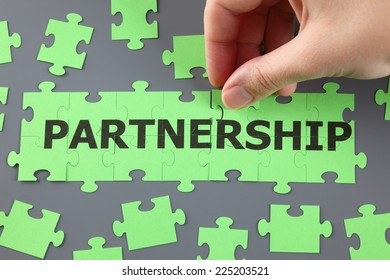 """Woman's hand completing  jigsaw puzzle with word """"Partnership""""."""