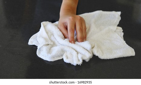 Woman's hand with cotton terry towel wiping stone counter