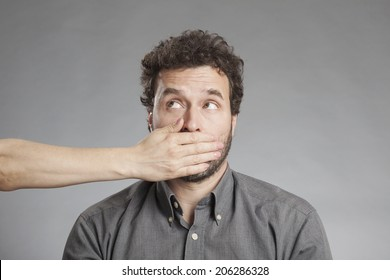 Woman's hand covering mature man's mouth