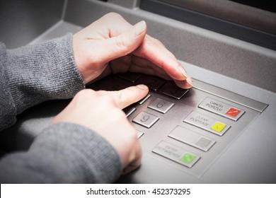 La mano de una mujer cubre su mano cuando introduce su PIN en un cajero automático