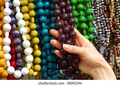 Woman's hand with different necklaces on the stall