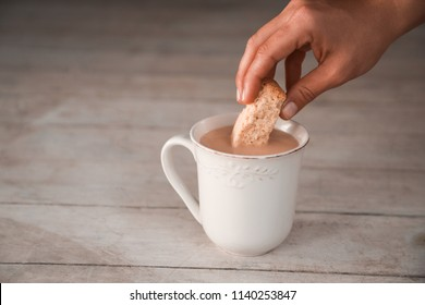 Woman's hand dipping a delicious rusk in hot tea, a favorite South African snack