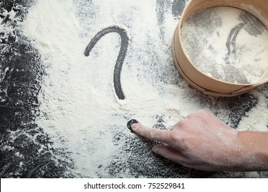 A woman's hand draws a question mark on flour. Sieve for flour and the concept of homemade cakes.
