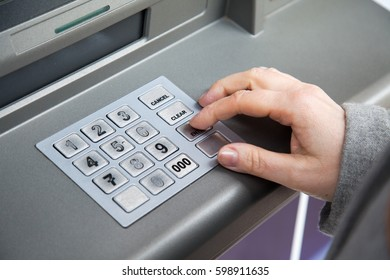 woman's hand enters the pin code into ATM