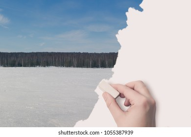 Woman's hand erased by the eraser of a winter landscape. Concept