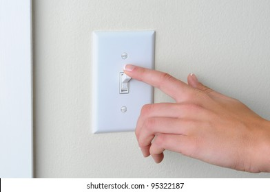 Womans hand with finger on light switch, about to turn off the lights. Closeup of hand and switch only. Horizontal format.