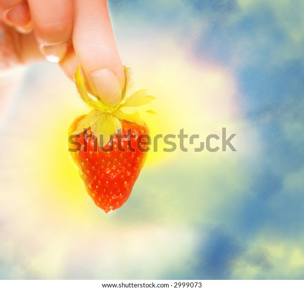 Woman's hand with a fresh strawberry