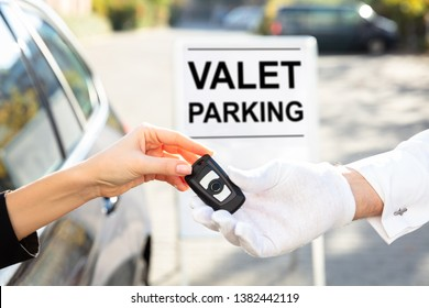 Woman's Hand Giving Car Key To Male Valet Near Valet Parking Sign