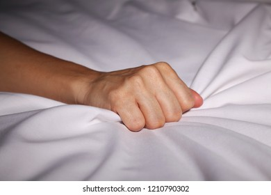 Woman's hand grabbing bed sheets during an orgasm
