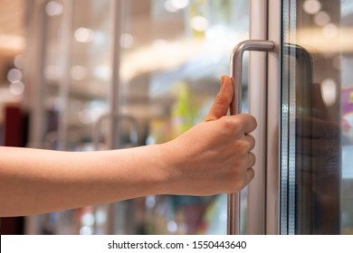 Woman's hand grabbing the handle of refrigerator in supermarket