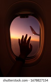 The woman's hand grabs the window glass on the plane and the light of the morning sunrise in the sky.