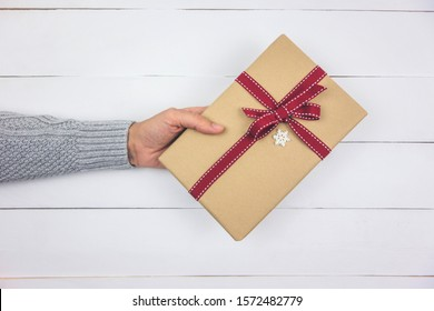 Woman's hand with gray sweater holding a Christmas present on white wood background. Top view.