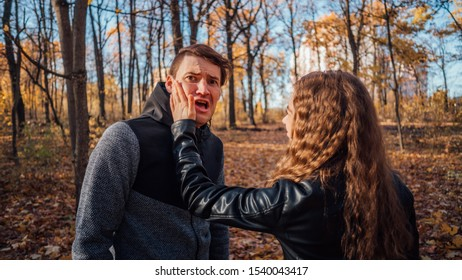 A woman's hand hits a man's face in the autumn forest. An emotional male is getting slapped in face, while shouting in a fear.