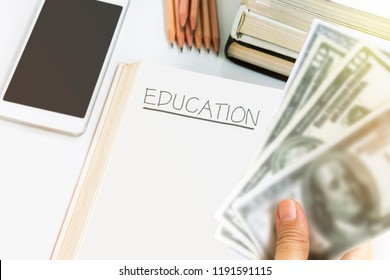A woman's hand hold a bitcoin with wooden pencil on the books open on the white table background with pile textbooks, banknote and smartphone. Money for education and business concept.