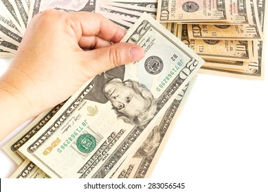 Woman's hand hold a twenty dollar bill on white background. Bills are background.