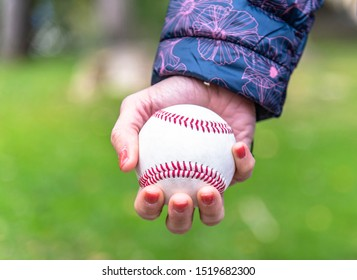 woman's hand holding baseball ball in the park