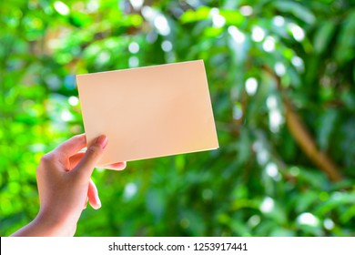 A woman's hand holding a blank empty yellow color paper wth green nature background.