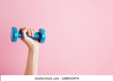Womans hand holding blue dumbbell isolated on pink background. Equipment for home workout. Fitness and activity. Sport and healthy lifestyle concept. Copy space in right side