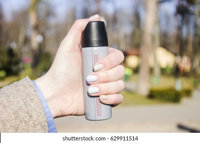 A woman's hand holding a  bottle of pepper spray
