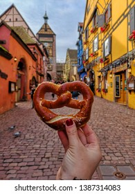 woman's hand holding a bretzel in alsace