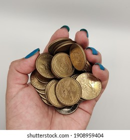 woman's hand holding a bunch of one dollar and half a dollar US coins money cash collector